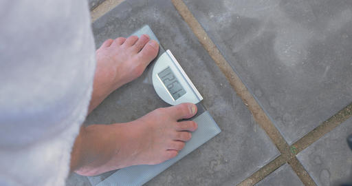 Man weighing himself on bathroom scales Footage