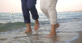 Couple Walking in Incoming Sea Waves Footage