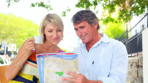 Smiling couple drinking coffee and checking the map Footage