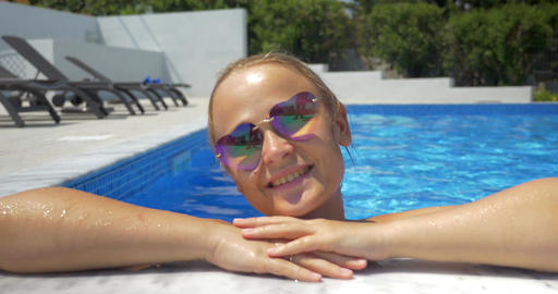Woman in sunglasses enjoying sunny day in the pool Footage