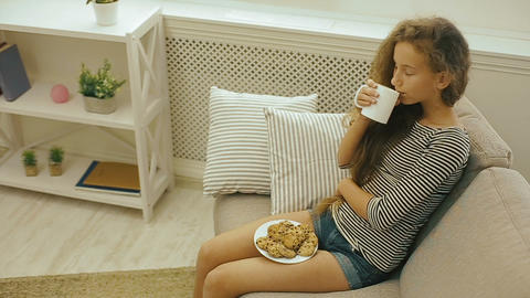 Young girl drinking fresh milk sitting on a sofa Archivo