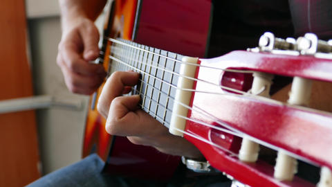 Close up of a young man playing a guitar Playing Acoustic Guitar Side Angle Archivo