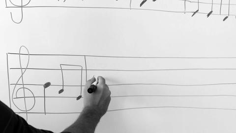 music teacher writes notes on the board, teaches notes Footage