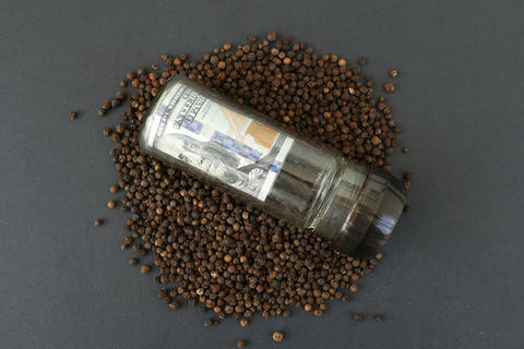 $ 100 in pepper box, dry peppercorns Photo