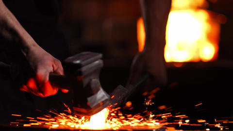 Closeup of a blacksmith's hammer on the background of burning flames of the Footage