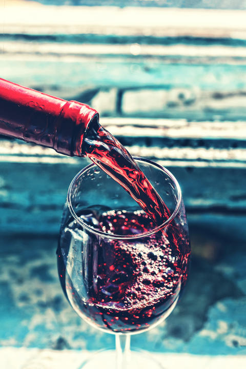 Pouring wine, Pouring red wine, glass, old wooden background Photo