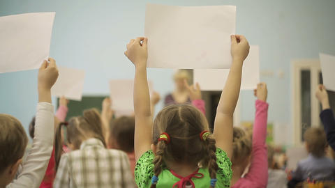 Children in the classroom are holding drawings in their hands Footage