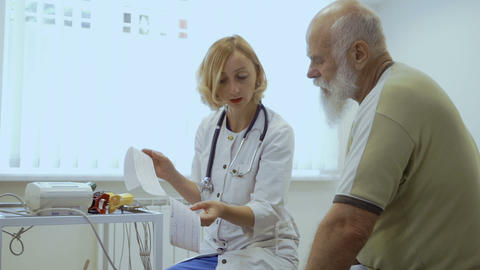 Doctor show results of electrocardiography to senior man Live Action
