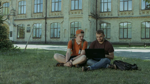 College students working on laptop on campus lawn Footage