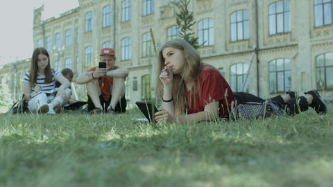 Thougthful student with tablet pc studying on lawn Footage