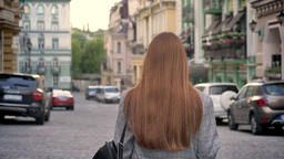 Young woman with long ginger hair walking in the city and holding backpack on Footage