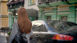 Young woman with long ginger hair walking in the street and holding backpack on Footage