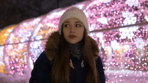 Portrait of a young beautiful girl. In the winter in the evening. She warms her GIF
