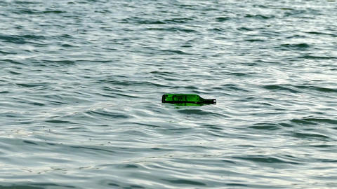a glass bottle drifting with waves, the bottle that hit the shore in the sea, Footage