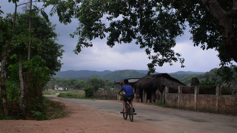 Wide shot of a kid cycling through a village road at Nongpho in Meghalaya GIF