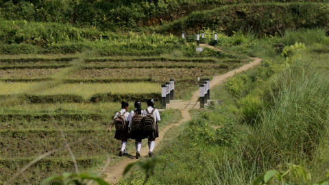 Wide shot of students walking through the village road in Nongpoh,in India ビデオ