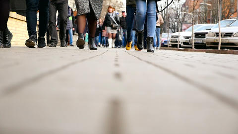 The feet of people are walking along the street. Without faces. Slow motion Footage
