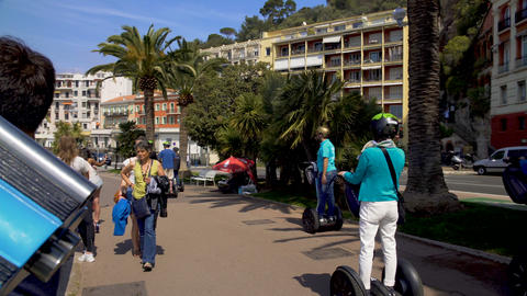 Tourists riding segways and strolling along seaside viewing platform, travel Footage