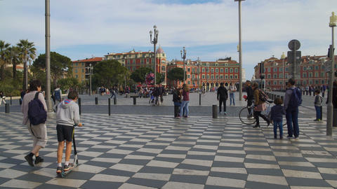 Carefree tourists and locals strolling along mosaic pavement of Massena square Footage