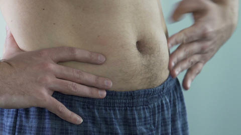 Close-up of man's stomach, male squeezing his belly at bathroom, close-up Live Action