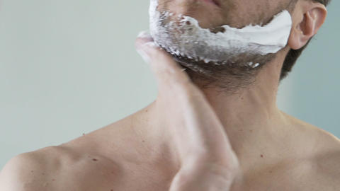 Man applying shaving foam on face skin, skincare and hygiene, morning ritual Live Action