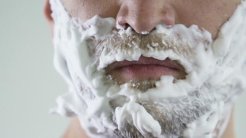 Lazy male applying shaving foam in front of mirror, skincare and hygiene Live Action