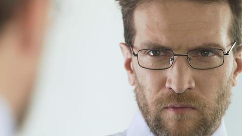 Serious businessperson choosing and wearing eyeglasses at optics store, eyesight Footage