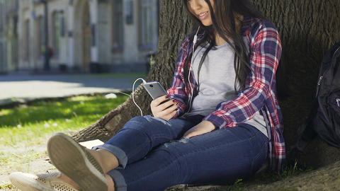 Girl sitting with phone on campus, chatting with friends and listening to music Footage