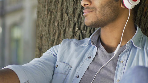 Thoughtful man listening to music in earphones, thinking about relationship Live Action