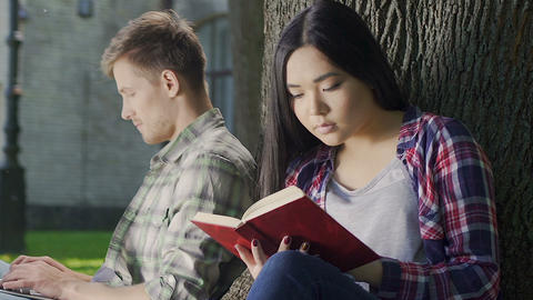 Biracial girl eagerly reading thrilling book without noticing guys loving looks Footage
