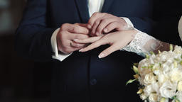 Hands of bride and groom exchanging wedding rings Footage