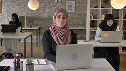 Three young muslim womans in hijab sitting and working in modern office, muslim Footage