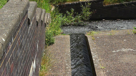 Water flowing down the canal into a small stream. Drinking water / sewer / ビデオ
