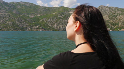 A young woman looks at the water and mountains Footage