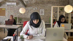 Three young muslim womens in hijab sitting and working in modern office, pretty Footage