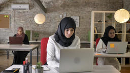 Three young muslim womens in hijab sitting and working in modern office, islamic Footage