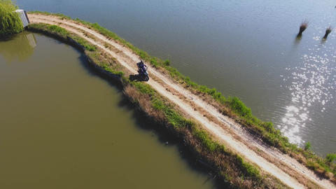 Aerial photography. Fishermen on a motorcycle. Fish pond. Summer morning Footage