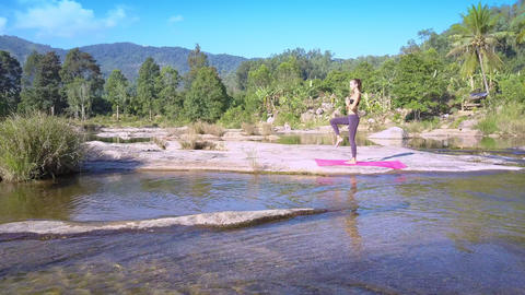 woman stands in yoga position against river with rapids GIF