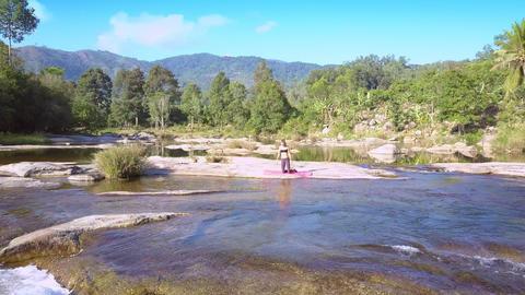 girl doing yoga on stone against mountain river GIF