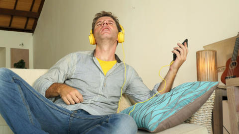 Young happy and attractive man at home living room couch listening to music with Archivo
