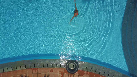 lady stands in pool and makes water circles Footage