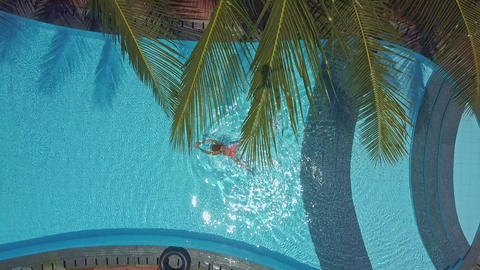 woman starts swimming along pool under palms Footage