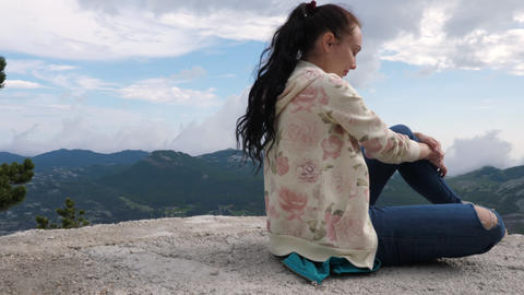 A girl looks into the distance at a high altitude Footage