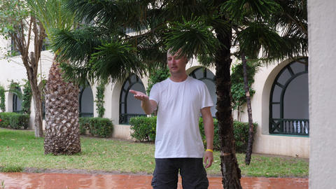 Man stands under tree branches during rain summer day and lookig on his palm at Footage
