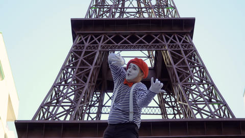 Mime in stripped shirt playing on invisible violin near Eiffel tower ビデオ