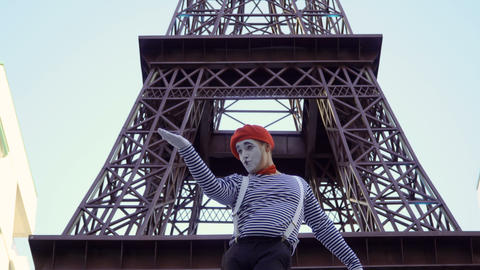 Funny man mime in red beret and stripped shirt playing near Eiffel tower ビデオ