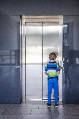 Little boy is calling the elevator フォト