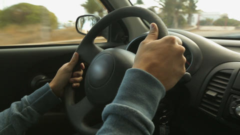 Masculine man's hands firmly holding steering wheel of car riding around city Live Action