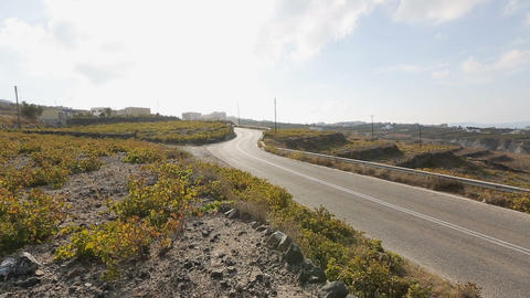 Lonely car driving along quiet road in mountainous terrain of Santorini island Footage