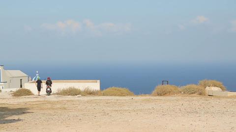 Religious tourists admiring view of church of panagia in Oia, Greece landmark Archivo